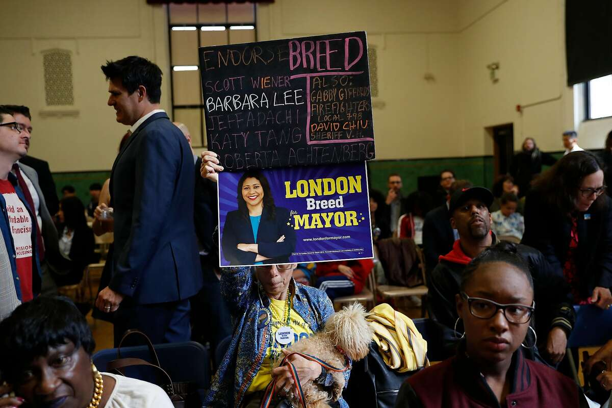Irene Dick-Endrizzi, with dog Bear, holds a sign as she waits for San Francisco Mayor-elect London Breed to appear at a mayoral campaign victory speech at Rosa Parks Elementary in San Francisco, Calif. on Thursday, June 14, 2018.