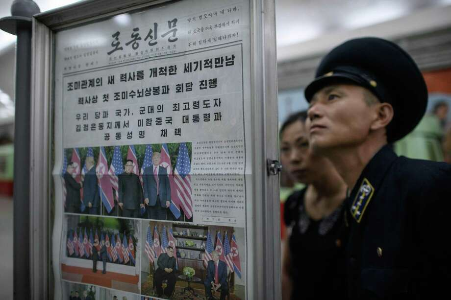 A conductor reads the latest edition of the Rodong Sinmun newspaper showing images of North Korean leader Kim Jong Un meeting with US president Donald Trump during their summit in Singapore, at a news stand on a subway platform of the Pyongyang metro on Wednesday. Photo: ED JONES /AFP /Getty Images / AFP or licensors