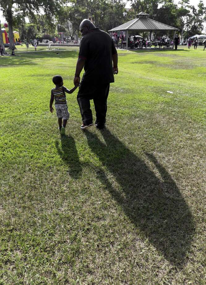 Three -year-old Joseph Hutchinson holds his father's Silvan Hutchinson hand as they walk across the park towards the Father's Day festivities June 15, 2014. African American parents have an opportunity to guide their children through matters of race. Photo: Craig Hartley /For The Chronicle / Copyright: Craig H. Hartley