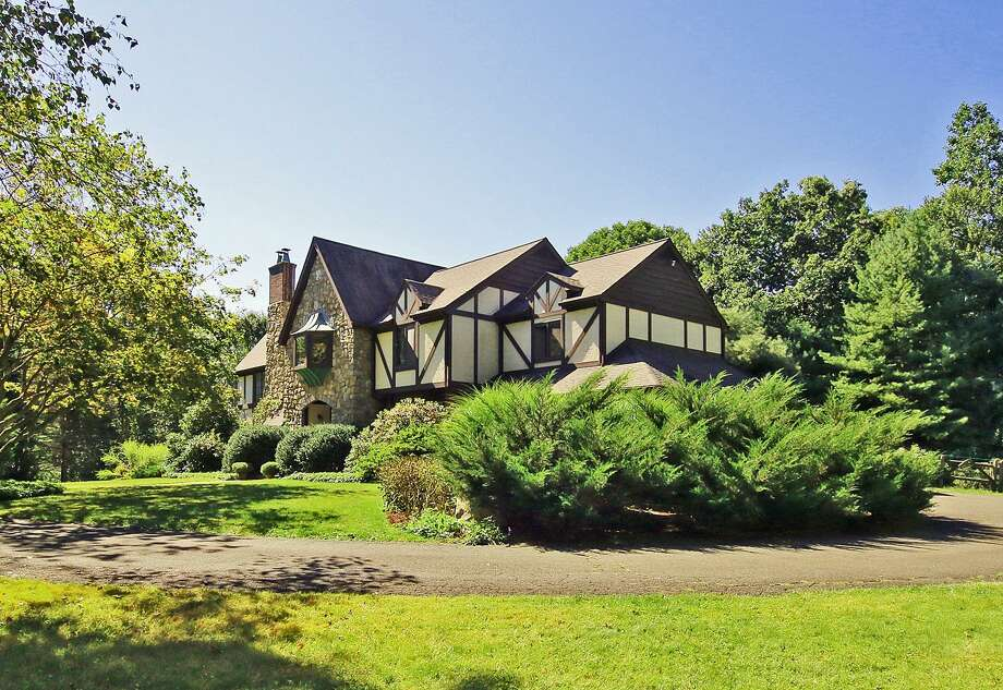 "The English-Tudor style home at 15 Tunxis Trail in Redding was custom built in 1983 by an Italian stone mason. The house includes a library loft accessed by a spiral staircase, vast gardens and a ""pub"" with a bar imported from England by one of the previous homeowners, a British rocker. Photo: Contributed Photo / Contributed / The News-Times Contributed"