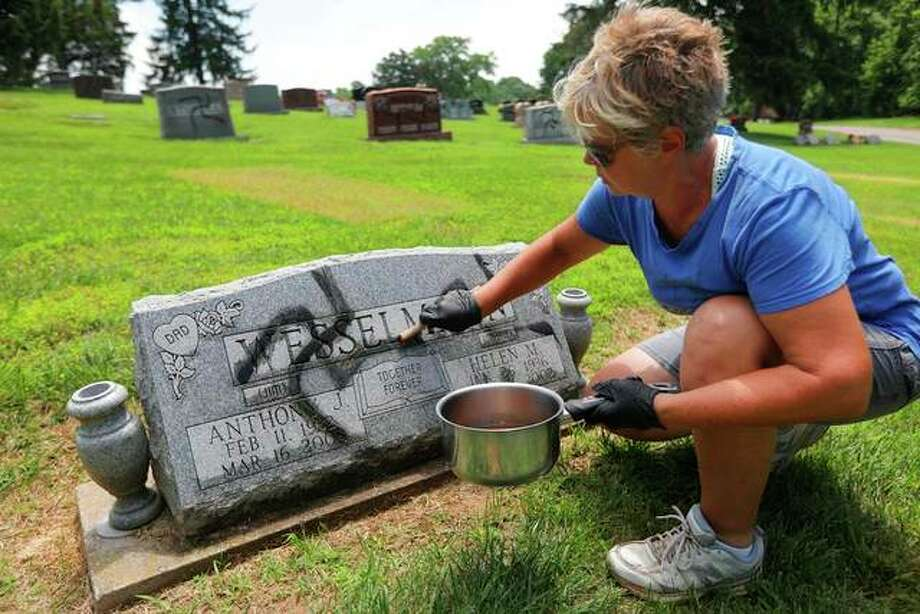 Tonya Johnson strips a painted swastika off a headstone at the Sunset Hill Cemetery in Glen Carbon, Ill., on Sunday, May 27, 2018, the day after employees at the cemetery found swastikas spray painted on more than 150 headstones. The man charged with the crime, Timothy V. McLean, was deemed unfit to stand trial by a judge Thursday. Photo:     Laurie Skrivan/St. Louis Post-Dispatch Via AP