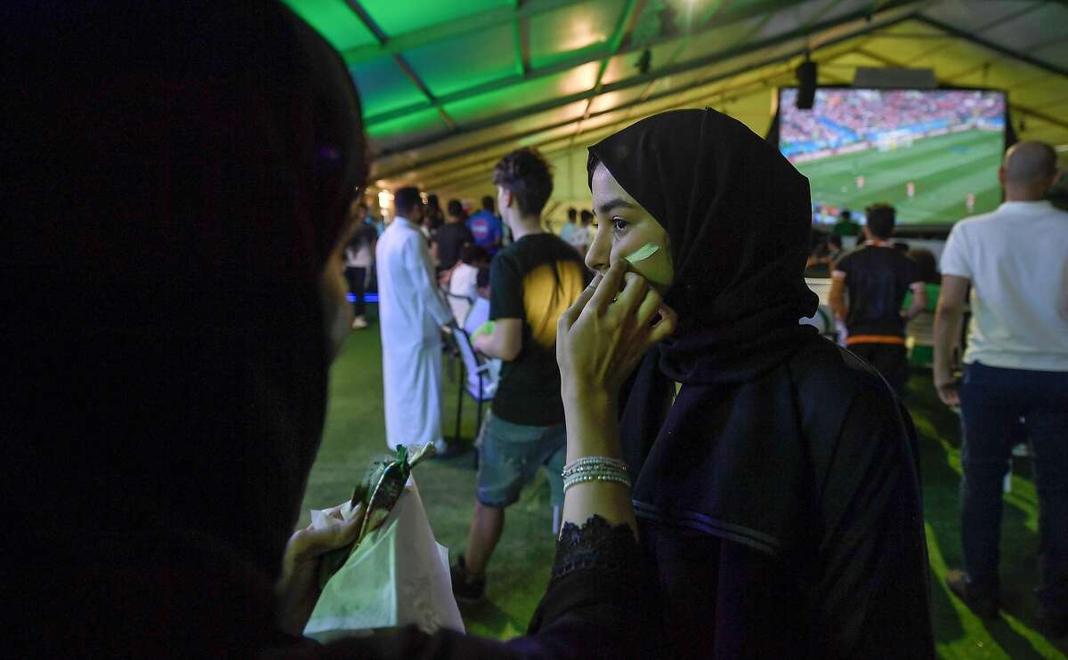 A Saudi woman football supporter has face paint applied to her a fan tent as the Russia 2018 World Cup Group A football match between Russia and Saudi Arabia is played behind, in the Red Sea coastal resort of Jeddah on June 14, 2018. / AFP PHOTO / Amer HILABIAMER HILABI/AFP/Getty Images