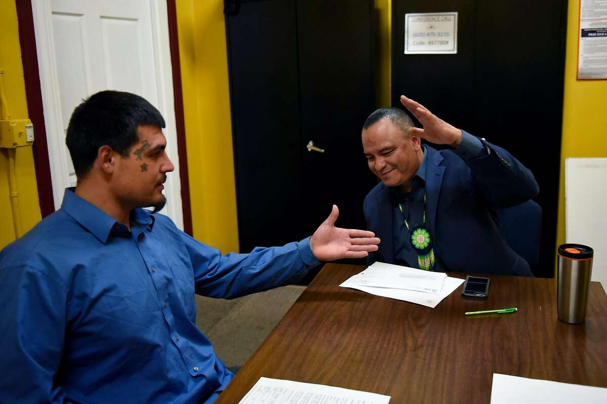Sammy Nunez, right, director of the non-profit Father and Families of San Joaquin, shakes hands with incoming team member Joseph Rivera, in their offices in Stockton, Calif., on Thursday June 14, 2018.