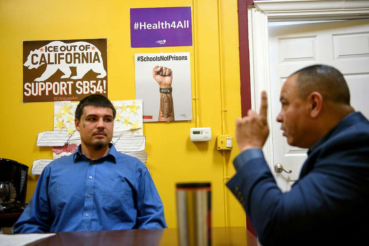 Political signs are seen on a wall as Sammy Nunez, right, director of the non-profit Father and Families of San Joaquin, speaks with incoming team member Joseph Rivera, in their offices in Stockton, Calif., on Thursday June 14, 2018.