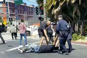 Police and bystanders drag a man from a burning car in Emeryville on Sunday.