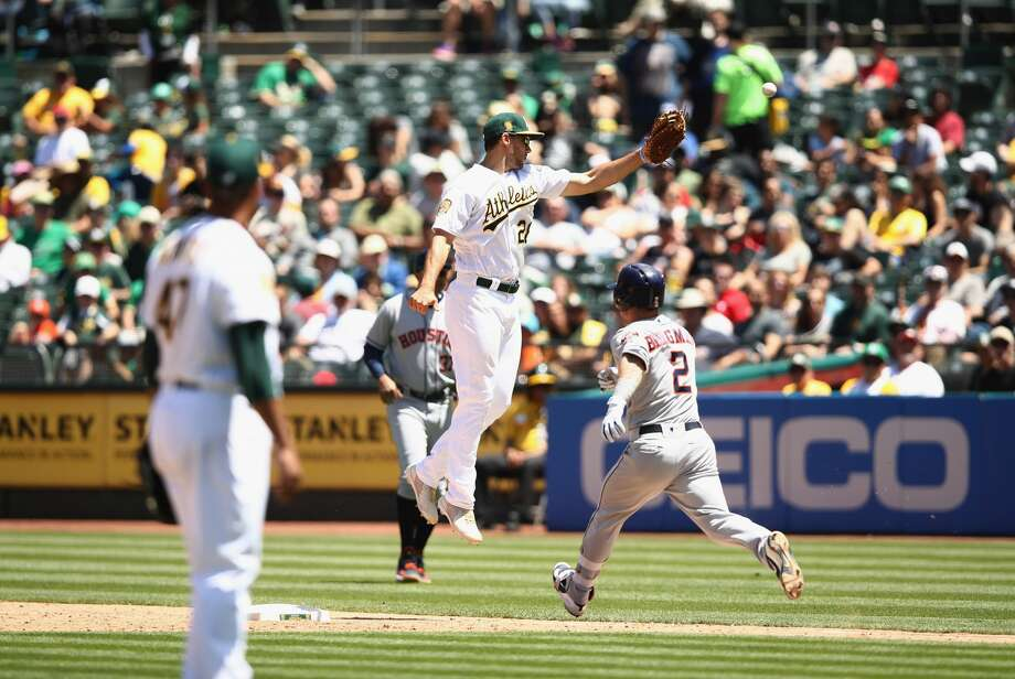 OAKLAND, CA - JUNE 14:  Alex Bregman #2 of the Houston Astros reaches first base safely after Matt Chapman #26 of the Oakland Athletics overthrows first baseman Matt Olson #28 in the sixth inning at Oakland Alameda Coliseum on June 14, 2018 in Oakland, California.  (Photo by Ezra Shaw/Getty Images) Photo: Ezra Shaw/Getty Images