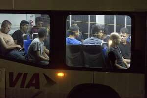 Apparently undocumented immigrants sit Tuesday night, June 12, 2018 in a VIA bus after being found in the back of an 18-wheel truck near loop 410 and Broadway.