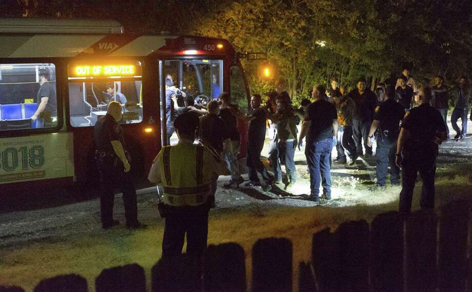 Apparently undocumented immigrants walk single file Tuesday night, June 12, 2018 to a waiting bus after being found in the back of an 18-wheel truck near loop 410 and Broadway. Photo: William Luther, Staff / San Antonio Express-News / © 2018 San Antonio Express-News