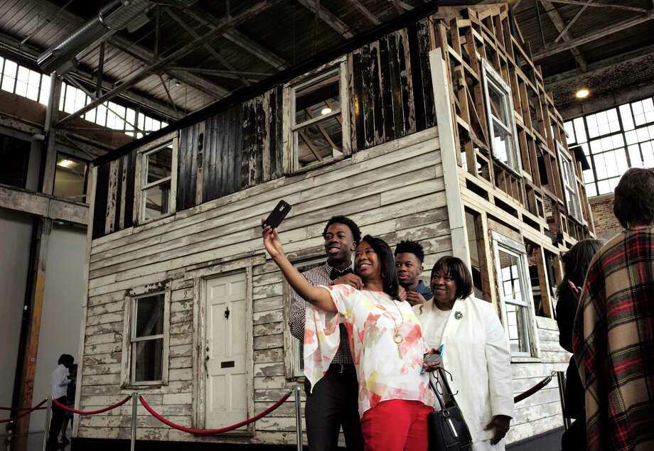 FILE - In this April 1, 2018 file photo, Cheryl Galloway, of Providence, R.I., uses a mobile phone to take a photo with family members in front of the rebuilt house of Rosa Parks at the WaterFire Arts Center in Providence, R.I. The house where Parks sought refuge in Detroit after fleeing the South will be auctioned after being turned into a work of art. Guernsey's auction house says the sale will be held mid-summer and that it's expected to fetch seven figures. (AP Photo/Steven Senne, File) Photo: Steven Senne / Copyright 2018 The Associated Press. All rights reserved.
