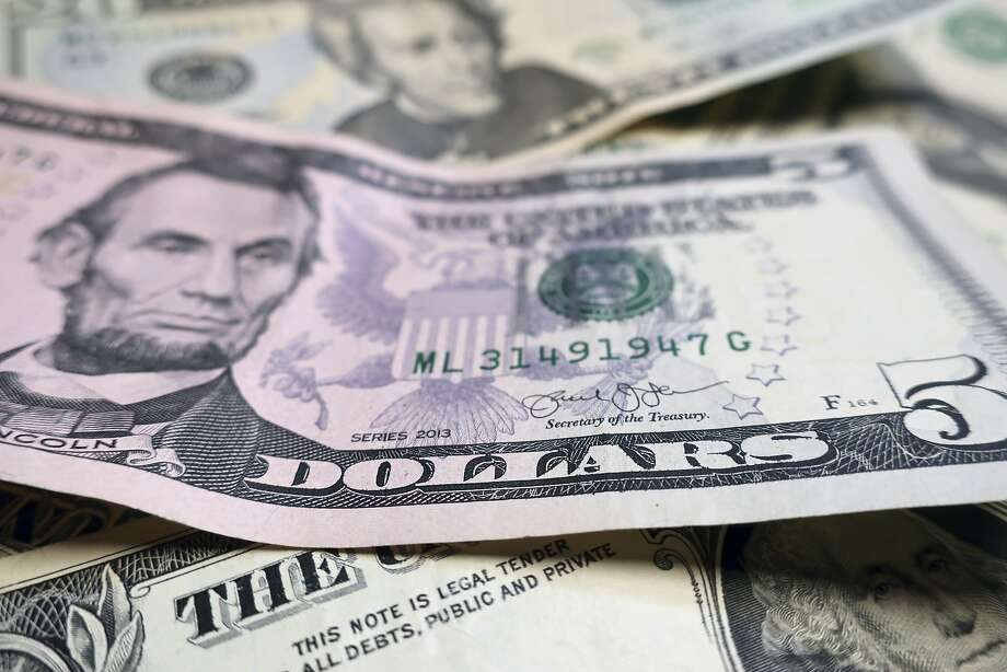 A Georgia man was charged with three counts of wire fraud this month for allegedly being a part of a romantic scam that left a San Francisco victim out of more than $100,000. FILE- Photo shows U.S. currency. Photo: Ted Shaffrey, Associated Press