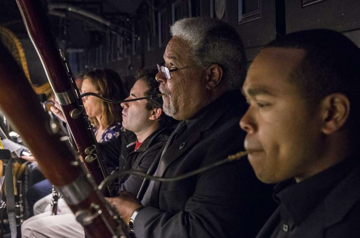 Rufus David Olivier (right) and father Rufus Olivier Jr. warm up in the orchestra pit before rehearsal at the War Memorial Opera House.