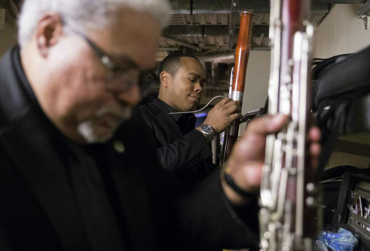 Rufus David Olivier (right), first substitute bassoonist for the S.F. Opera Orchestra, and dad Rufus Olivier Jr., the first-chair bassoonist, put together their instruments before a dress rehearsal for the