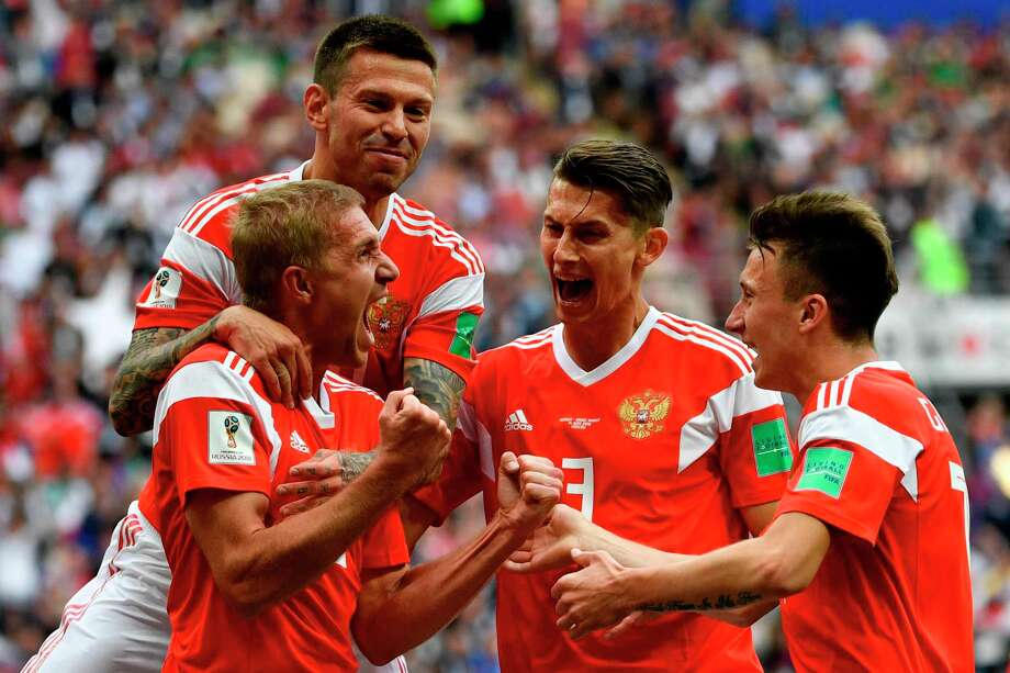 TOPSHOT - Russia's midfielder Yuri Gazinskiy (L) celebrates scoring the opening goal with his teammates during the Russia 2018 World Cup Group A football match between Russia and Saudi Arabia at the Luzhniki Stadium in Moscow on June 14, 2018. / AFP PHOTO / Alexander NEMENOV / RESTRICTED TO EDITORIAL USE - NO MOBILE PUSH ALERTS/DOWNLOADSALEXANDER NEMENOV/AFP/Getty Images Photo: ALEXANDER NEMENOV / AFP or licensors