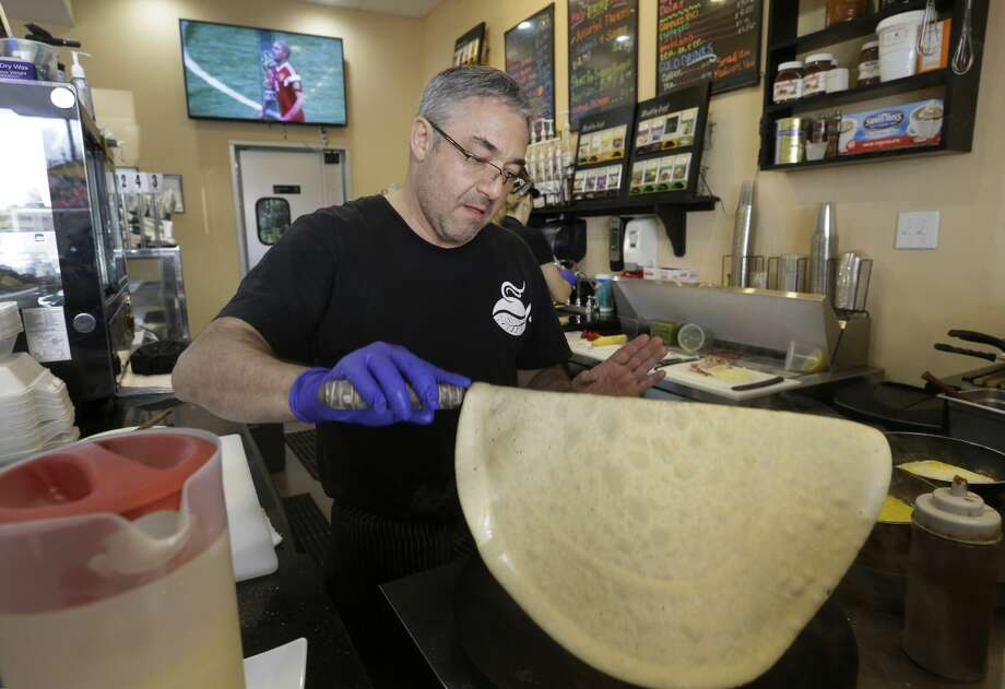 Owner Mikhail Goryachev makes crepes at Nyam Nyam Café, 15201 Mason Road, as Russia plays against Saudi Arabia in the FIFA World Cup on the television in the background Thursday, June 14, 2018, in Cypress. Photo: Melissa Phillip/Houston Chronicle