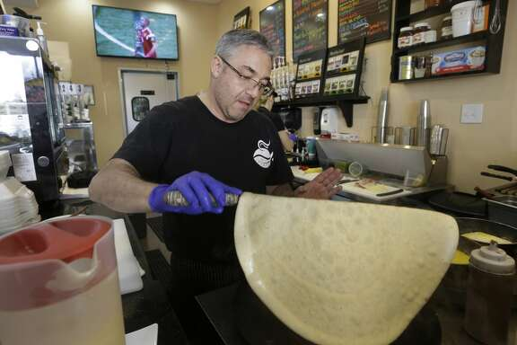 Owner Mikhail Goryachev makes crepes at Nyam Nyam Café, 15201 Mason Road, as Russia plays against Saudi Arabia in the FIFA World Cup on the television in the background Thursday, June 14, 2018, in Cypress.