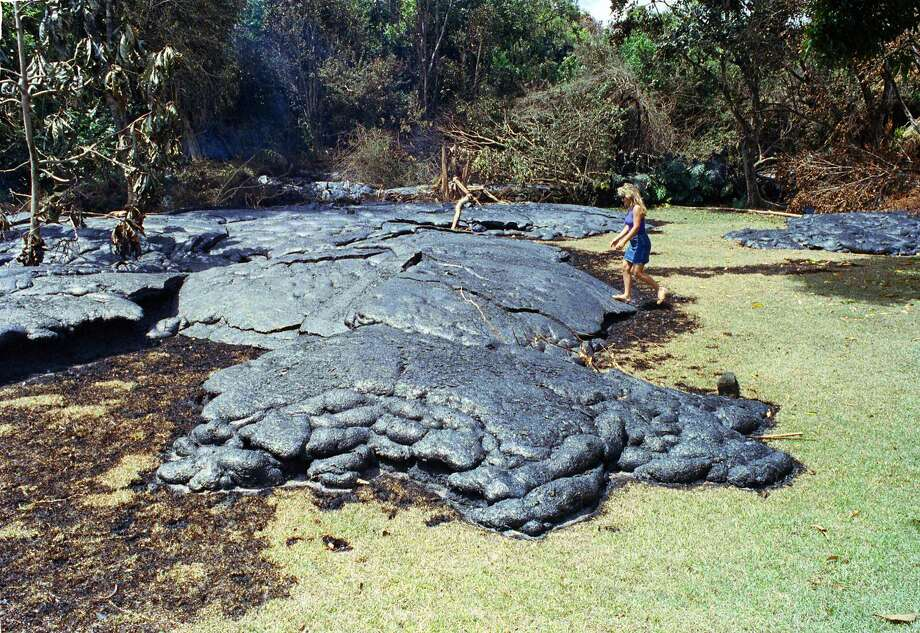 A 1990 photo shows Mary Dressler stepping on a cooled lava flow that had inundated the backyard of her mother-in-law's home in Kalapana. Dressler's home was destroyed. Photo: Gary Stewart / Associated Press 1990