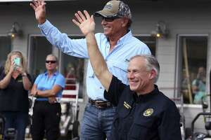 "FILE - In this Sept. 21, 2017, file photo, George Strait, left, and Texas Gov. Greg Abbott wave to the crowd in Rockport, Texas, during a visit with individuals affected by Hurricane Harvey. Strait leads a new tourism campaign for Hurricane Harvey-damaged Rockport and Fulton nearly 10 months after the storm devastated the area he sometimes calls home. Officials with the Rockport-Fulton Chamber of Commerce say Strait, who's owned a house in the community for years, participated free of charge. Strait is part of the ""Find Yourself in Rockport-Fulton"" radio and TV campaign to encourage tourists to return to the area hard-hit when Harvey made landfall in August. (Rachel Denny Clow/Corpus Christi Caller-Times via AP, File)"