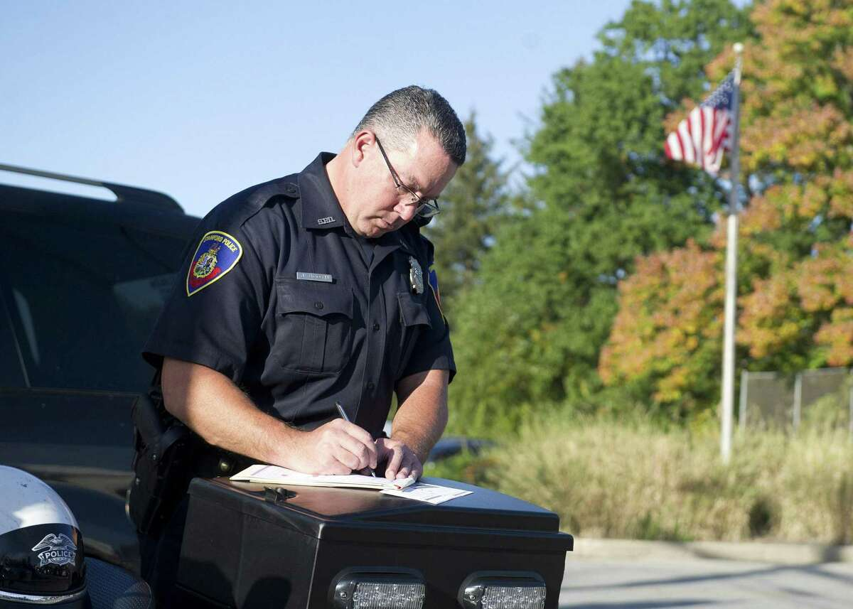 Stamford Police Officer Jeff Booth tickets drivers during a traffic stop for all violations, including blocking the box, at the intersection of Palmer Hill Road and Westover Road in Stamford, Conn., on October 3, 2014.