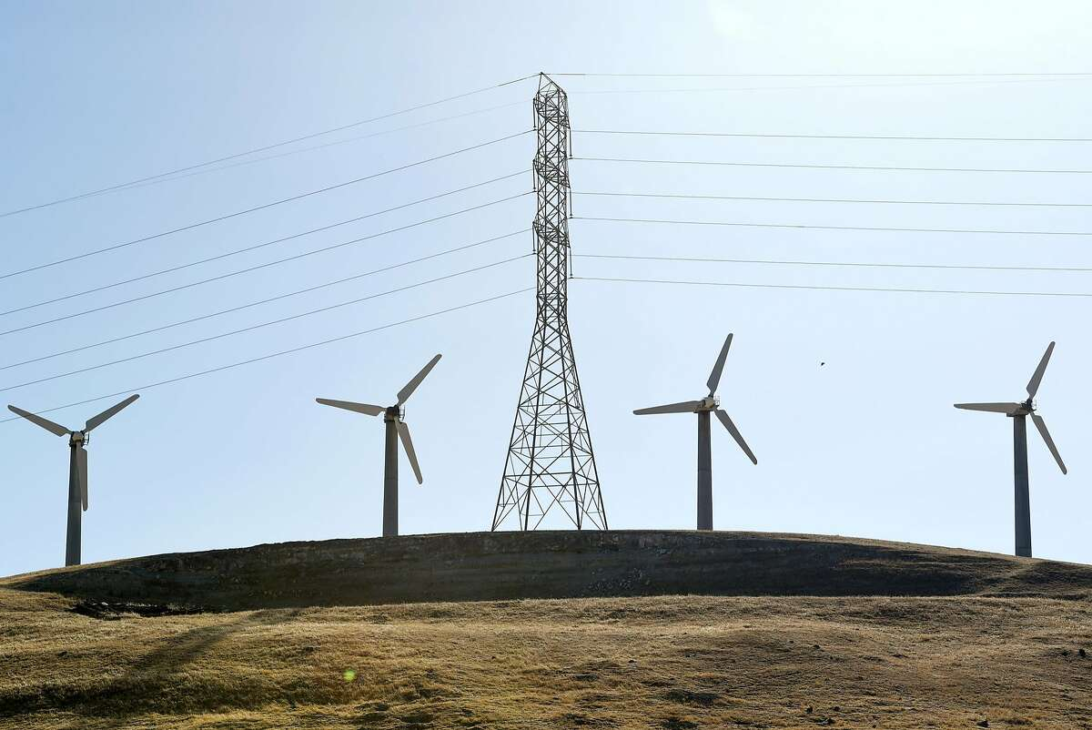 Wind turbines are seen near high tension power lines outside of Tracy, Calif., on Thursday June 14, 2018.