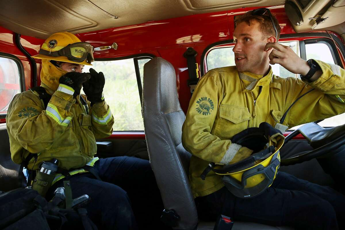 From left: Marin County Fire Department trainee Tim McDevitt with firefighter and instructor Tyler Fiske during wildfire training, Wednesday, June 13, 2018, in San Rafael, Calif.