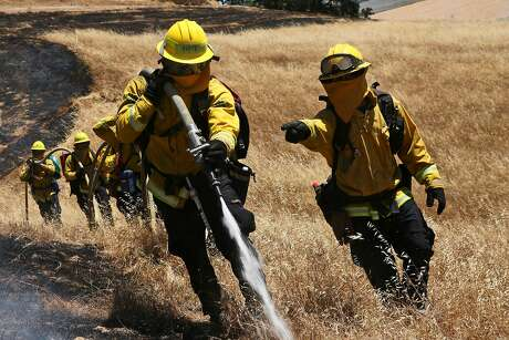 Marin County Fire Department firefighter trainees work together to extinguish a fire during wildfire training, Wednesday, June 13, 2018, in San Rafael, Calif.