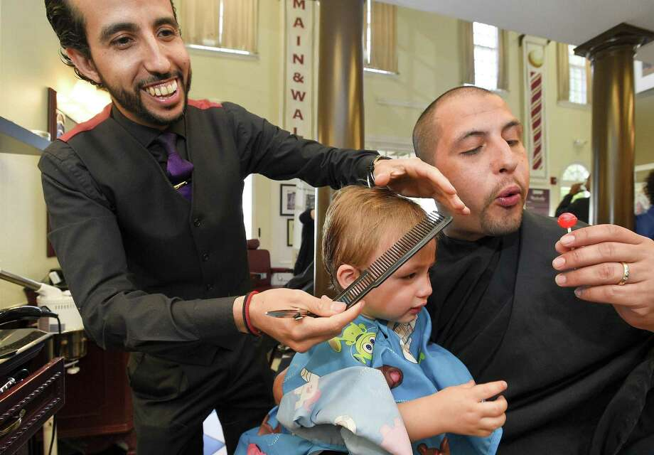 Nathan Otero blows hair clippings from a lollipop his son Cameron was enjoying as Rudy Yazidi, a Master Barber at Kennedy's Barber Club, styles the one and half year-old  hair  on June 14, 2018 in Darien, Connecticut. Otero successfully completed the Exchange Club of Stamford's Fatherhood 24:7 program. The class, offered by the Exchange Club Parenting Skills Center, takes a home-based approach to teach fathers how to become more involved, responsible and committed parents. Graduates and their families were offer free grooming and styling by Kennedy's Barber Club. Photo: Matthew Brown / Hearst Connecticut Media / Stamford Advocate