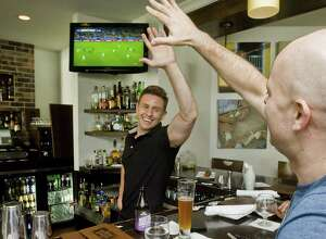 Bartender Keith Maloney high-fives patron Ryan Buzzell of Danbury during the action of the World Cup championship soccer match between Germany and Argentina in 2014 at Mezon Tapas Bar & Restaurant on Mill Plain Road in Danbury.
