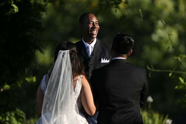 Pastor Darrell Ross (center) officiates the wedding between LeAnn Coto (left) and Douglas Coto at the Martinelli Event Center, Saturday, June 2, 2018, in Livermore, Calif.