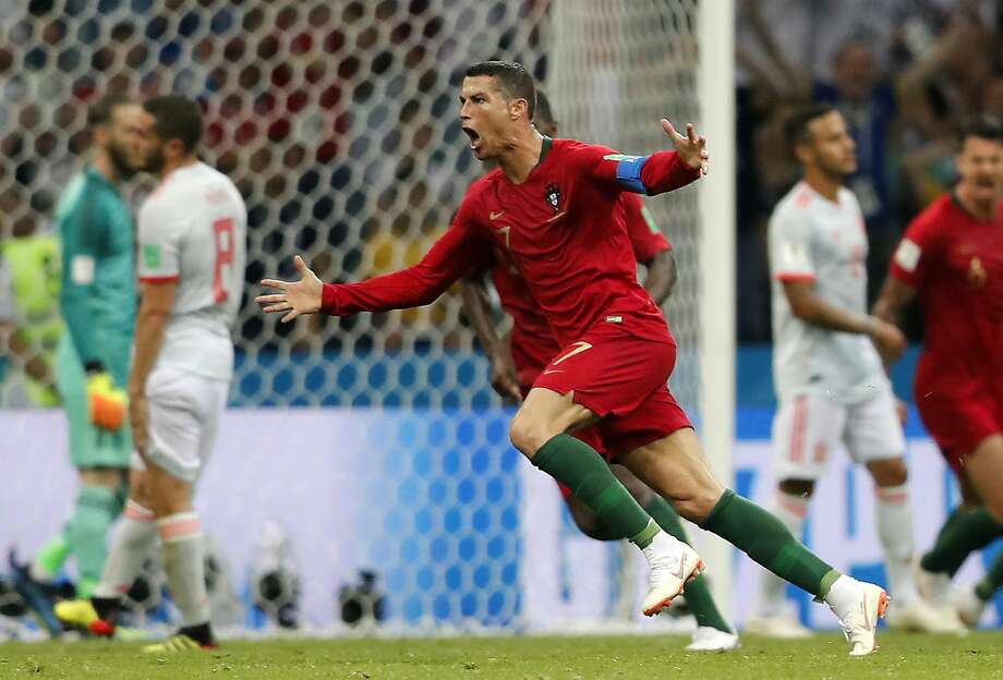 Portugal's Cristiano Ronaldo celebrates after he scored his third goal with a free kick during 88th minute against Spain in the World Cup opener for both. Photo: Frank Augstein / Associated Press