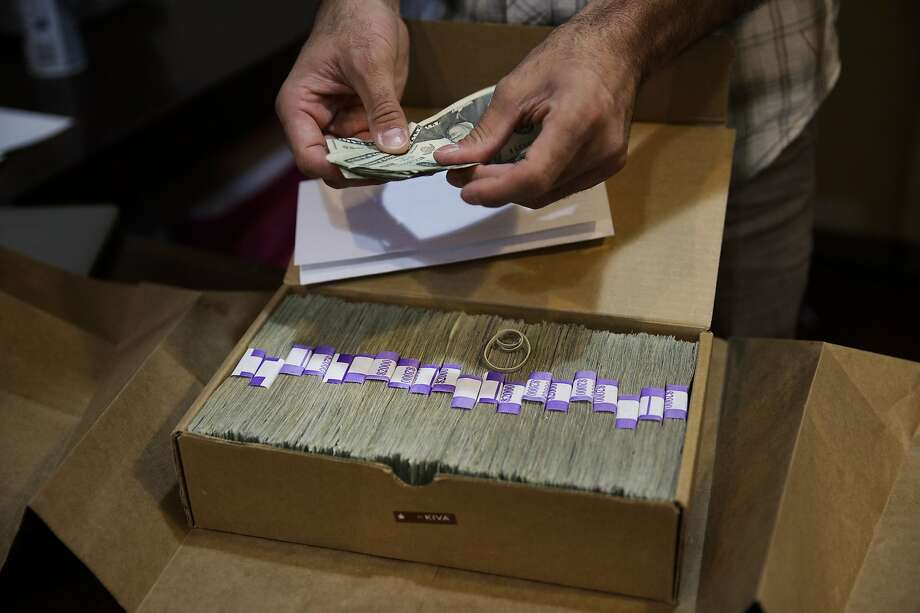 FILE - In this June 27, 2017 file photo, the proprietor of a medical marijuana dispensary prepares his monthly tax payment, over $40,000 in cash, at his Los Angeles store.  A proposal in Congress to ease the federal ban on marijuana could encourage more banks to do business with cannabis companies, but it appears to fall short of a cure-all for an industry that must operate mainly as a cash business in a credit card world.   (AP Photo/Jae C. Hong, File) Photo: Jae C. Hong / Associated Press 2017