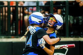 Coleman sophomore Abigail Tubbs, left, hugs junior MacKenzie Miller after Miller scored the first run of the game during the Comets' 2-0 Division 4 state softball semifinals victory over Rogers City on Friday, June 15, 2018 at Michigan State University. (Katy Kildee/kkildee@mdn.net)