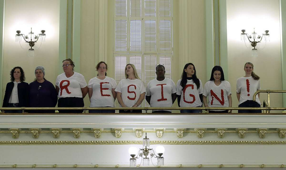 Protestors calling on Assemblywoman Cristina Garcia, D-Bell Gardens, to resign from office, stand in the Assembly gallery, Friday, May 25, 2018 in Sacramento, Calif. The protesters are part of an effort by labor organizations and building trade groups aiming to oust Garcia. Garcia took a three-month leave of absence after a groping allegation and other claims of inappropriate behavior surfaced. Outside investigators cleared her of the groping claim but found she used vulgar language in violation of the Assembly's sexual harassment policy. (AP Photo/Rich Pedroncelli)