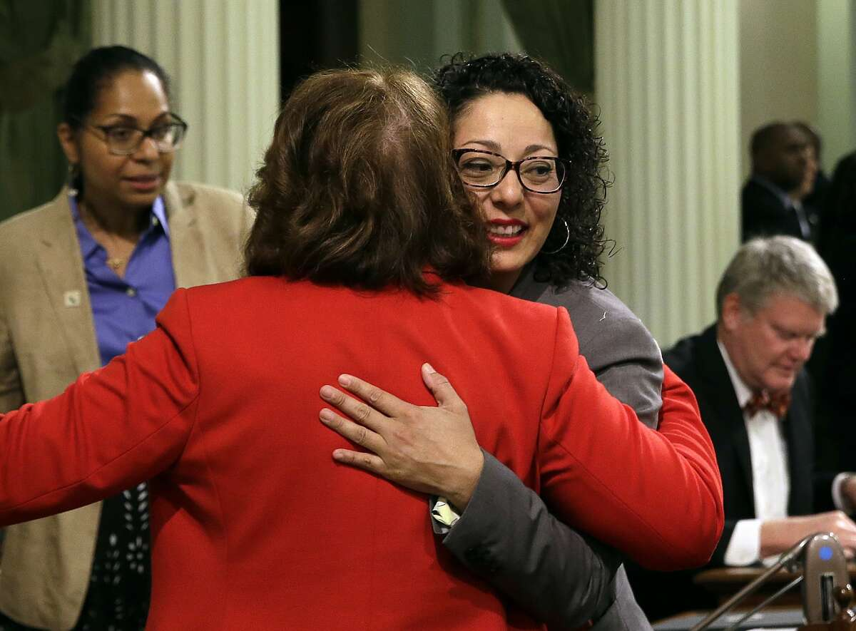 Assemblywoman Cristina Garcia, D-Bell Gardens, right, is hugged by Assemblywoman Eloise Gomez Reyes, D-Grand Terrace, on her first day back in the Assembly since an investigation into sexual misconduct charges, Friday, May 25, 2018, Sacramento, Calif. Garcia took a three-month leave of absence after a groping allegation and other claims of inappropriate behavior surfaced. Outside investigators cleared her of the groping claim but found she used vulgar language in violation of the Assembly's sexual harassment policy. (AP Photo/Rich Pedroncelli)