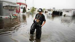Andres Martinez, R.C. Mobile Park resident, returns to his home after developing a leak in two garbage bags he had fashioned into home made waders while trying to check on his parents home at the flooded R.C. Mobile Park on Friday, December 12, 2014 in Redwood City, Calif.