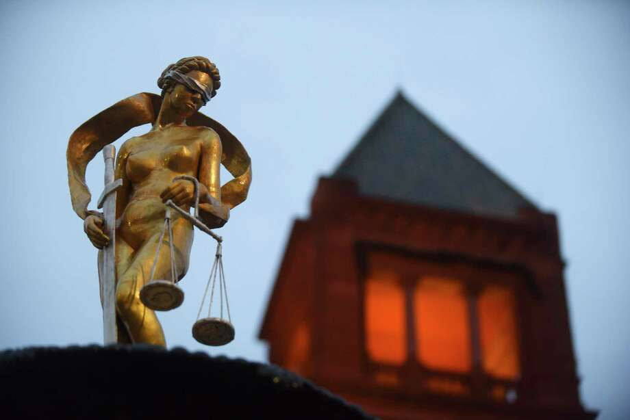 The Lady Justice statue atop a fountain in front of the Bexar County Courthouse gleams after a refurbishing last year. The state of indigent defense in the county may not be as lustrous. Photo: Billy Calzada / / San Antonio Express-News