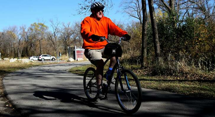 A cyclist pedals down Salado Creek Greenway, one of many linear parks in the city.