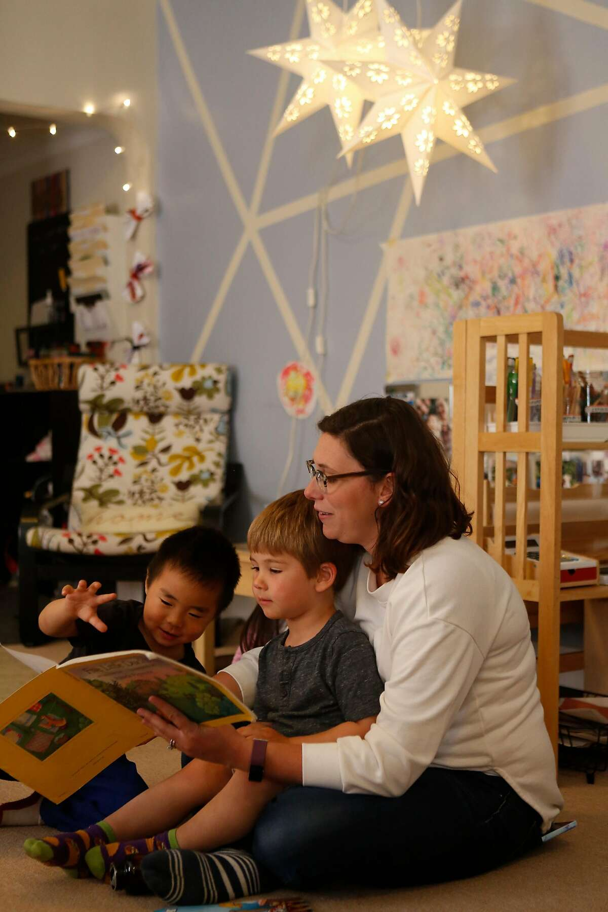 Kristina Gonzalez, reads a book to preschool students Luca, center, and Zane, left, at her home on Thursday, June 14, 2018 in San Francisco, Calif. Gonzalez operates Little Robles, a Spanish immersion program, that was born from Wonderschool, a start-up that helps people create preschools in their homes.