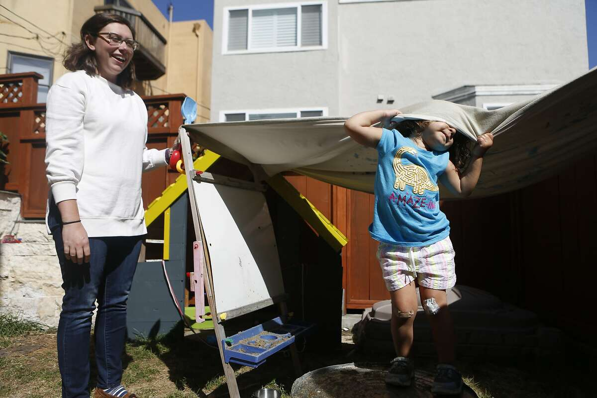 Annalia plays outside at an in-home preschool while teacher Kristina Gonzalez watches on Thursday, June 14, 2018 in San Francisco, Calif.