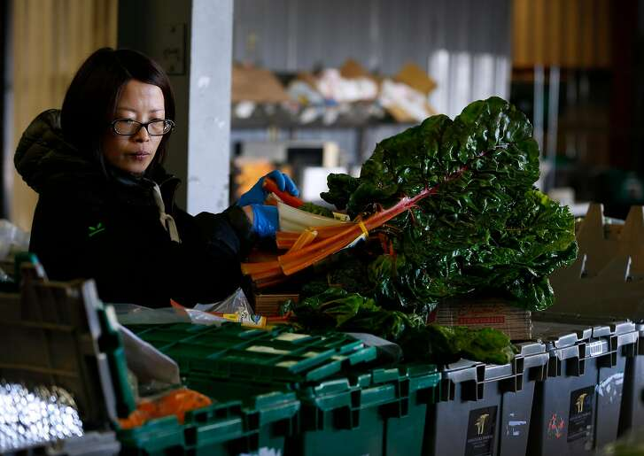 Angela Du fills orders of fresh produce for customers at the GrubMarket warehouse in San Francisco, Calif. on Friday, June 15, 2018.