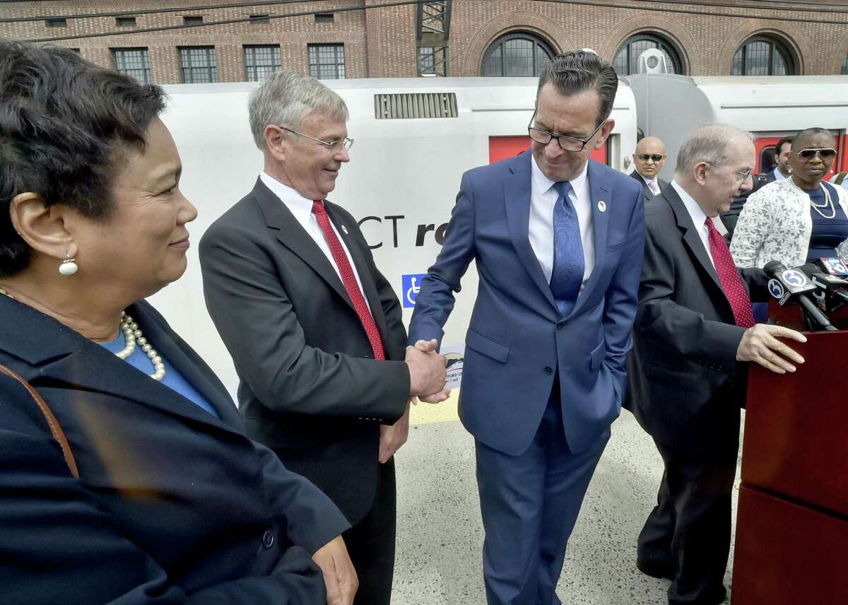 New Haven, Connecticut - June 15, 2018: CTDOT Commissioner James Rekeder and Governor Dannel P. Malloy enjoy a congratulatory handshake as New Haven Mayor Toni Harp, left, State Senator Martin Looney, fourth from left, and State Representative Robyn Porter D-New Haven, far right, participate in the a grand opening ceremony for the new CTrail Hartford Line Connecticut Rail commuter service launched Friday at Union Station Friday, June 15 with a train starting at Union Station in New Haven to Hartford with stops in New Haven's State Street station, Wallingford, Meriden, Berlin and Hartford. The Springfield Line train starts in Springfield, Massachusetts with stops at Windsor Locks, Windsor and Hartford. The main grand ceremony Tuesday took place at Hartford's Union Station.