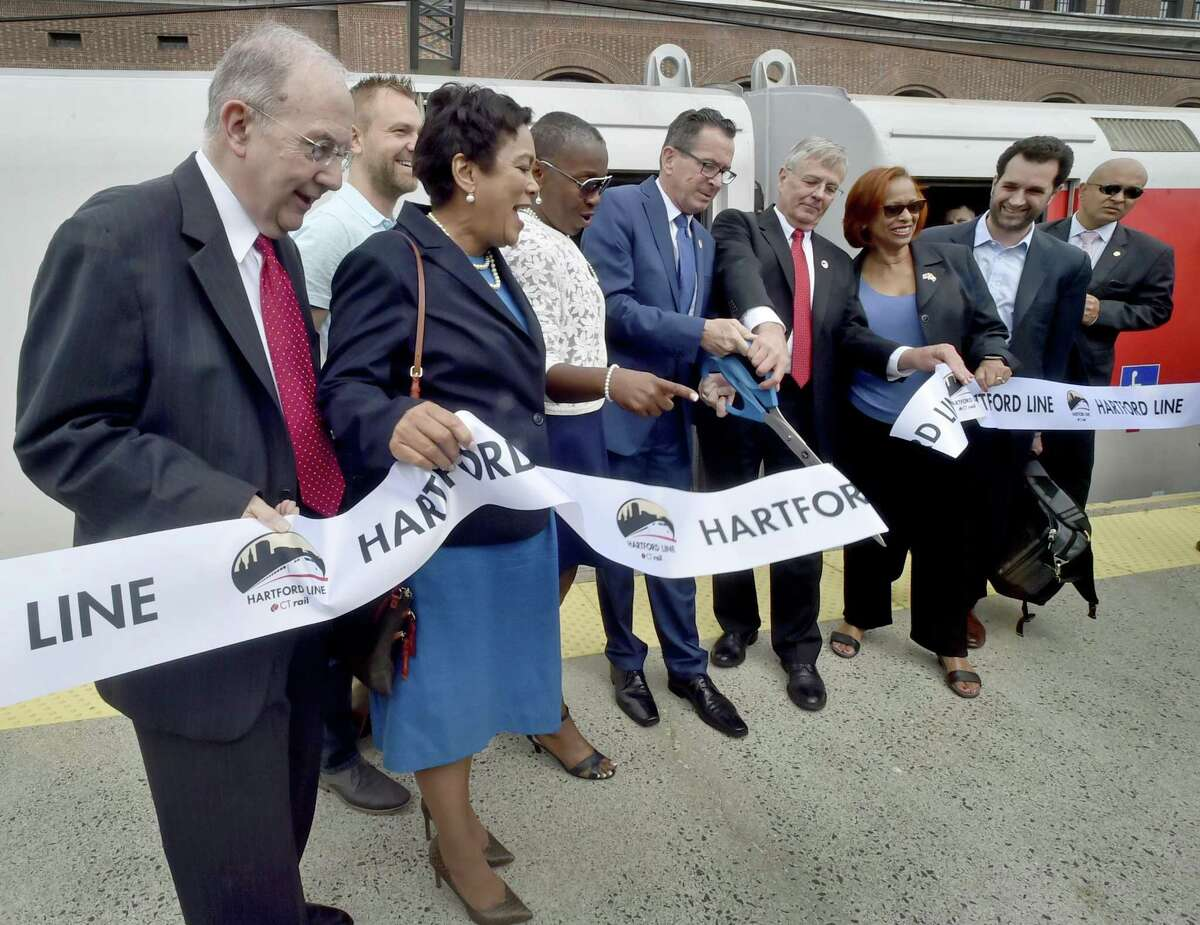 New Haven, Connecticut - June 15, 2018: State Senator Martin Looney, New Haven Mayor Toni Harp, State Representative Joshua Elliott D-Hamden, State Representative Robyn Porter D-New Haven, Governor Dannel P. Malloy, CTDOT Commissioner James Redeker State Representative Toni Walker D-New Haven, and State Representative Mike D'Agostino D-Hamden, left to right, cut the ribbon during a ceremony for the new CTrail Hartford Line Connecticut Rail commuter service launched Friday at Union Station Friday, June 15 with a train starting at Union Station in New Haven to Hartford with stops in New Haven's State Street station, Wallingford, Meriden, Berlin and Hartford. The Springfield Line train starts in Springfield, Massachusetts with stops at Windsor Locks, Windsor and Hartford. The main grand ceremony Tuesday took place at Hartford's Union Station.