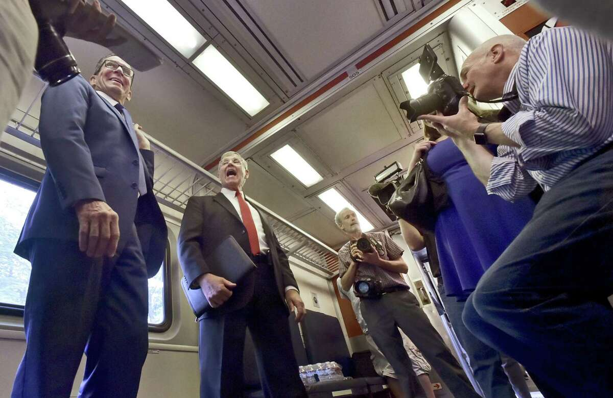 New Haven, Connecticut - June 15, 2018: Governor Dannel P. Malloy, left, and CTDOT Commissioner James Redeker talk with the press while traveling on the inaugural run of the new CTrail Hartford Line Connecticut Rail commuter service from New Haven to Hartford launched Friday with frequent train service between New Haven, Hartford and Springfield. The grand ceremony Friday took place at Hartford's Union Station upon Malloy's and Redeker's arrival.