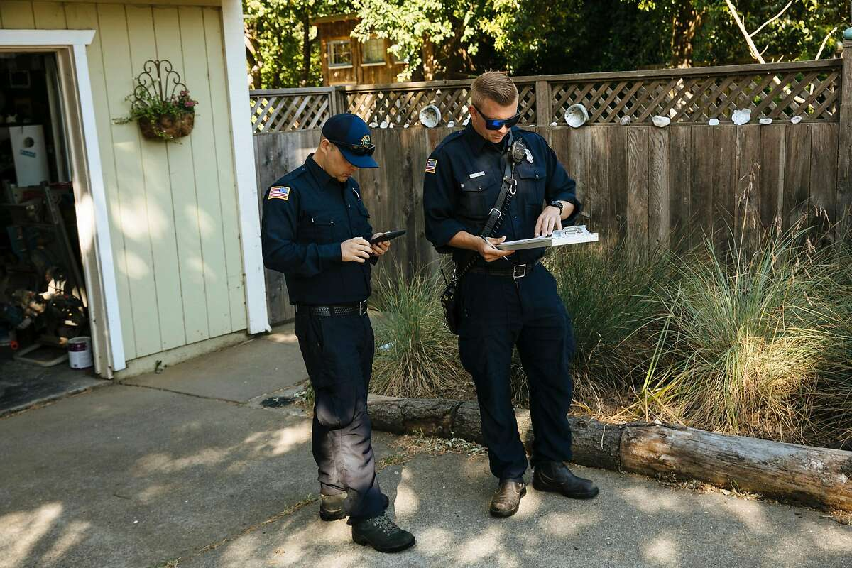 Marin County firefighters, Cole Rippe and Alex Mercer go through a check list of recommendations for a property during a defensible space inspection in Woodacre, Calif., Wednesday, June 6, 2018.
