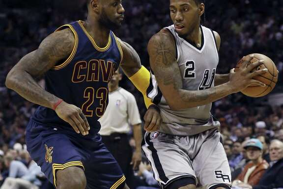 Cleveland Cavaliers' LeBron James defends San Antonio Spurs' Kawhi Leonard during first half action Thursday March 12, 2015 at the AT&T Center.