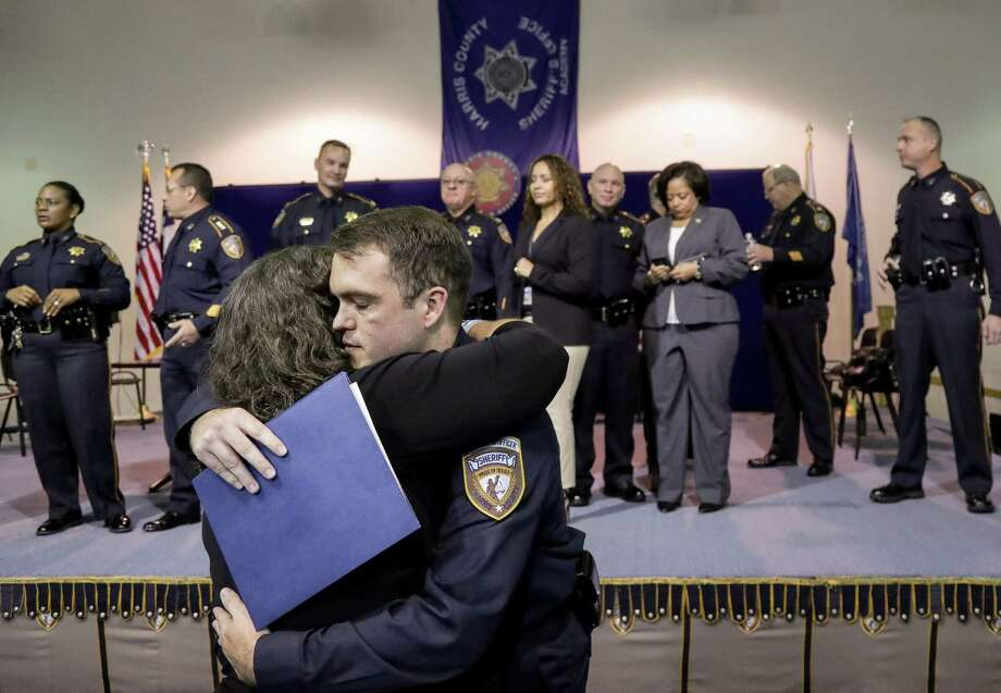 """Charles Greenwood hugs his mother, Patricia Greenwood, after graduation from the Basic County Corrections Course, at the Harris County Sheriff's Office Academy, Friday, June 15, 2018, in Houston. Greenwood is the son of slain Precinct 3 Assistant Chief Deputy Constable Clint Greenwood, and he is joining the Harris County Sheriff's Office as a detention officer. """"I think tradition is seeing what became important to them and following that,"""" Greenwood said. Photo: Jon Shapley, Houston Chronicle / Houston Chronicle / © 2018 Houston Chronicle"""