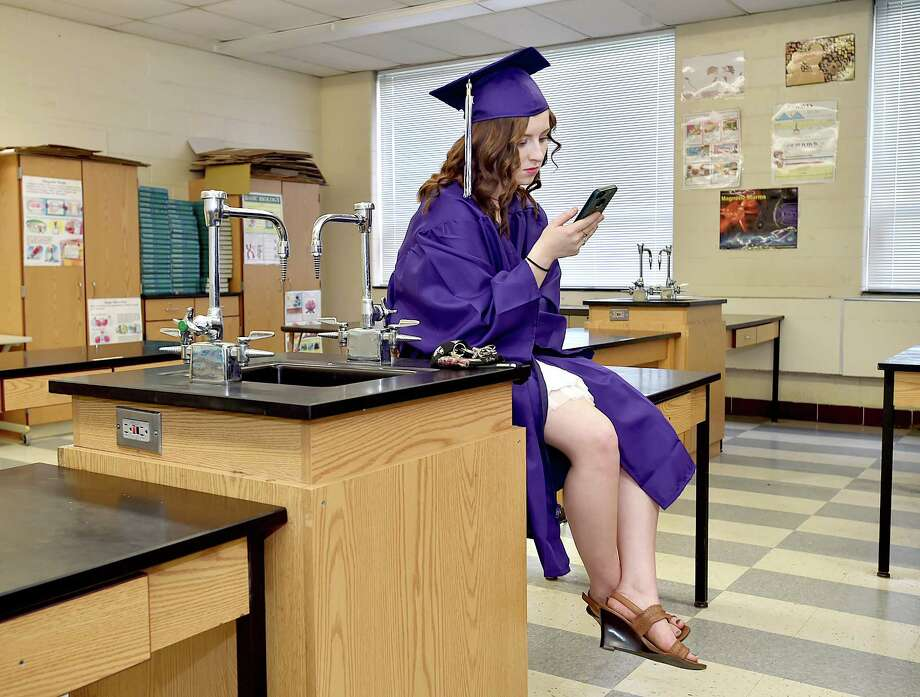 Alannah Miessau texts her boyfriend Alex from a chemistry lab before commencement exercises begin at North Branford High School, Friday, June 15, 2018. Photo: Catherine Avalone, Hearst Connecticut Media / New Haven Register