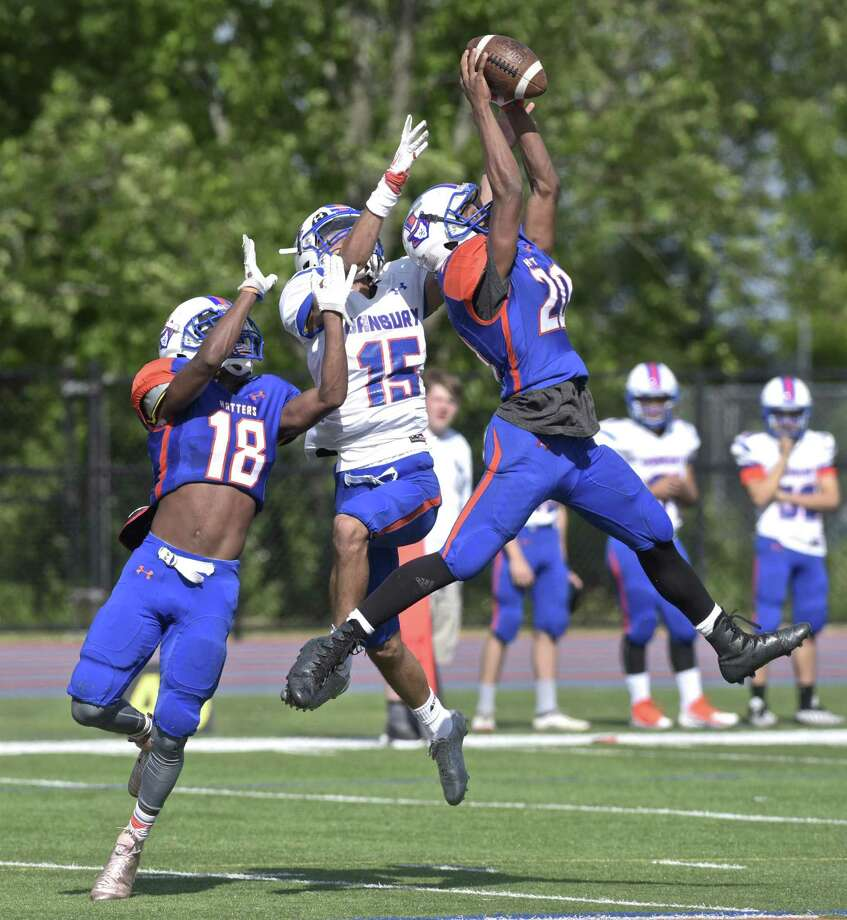 Sylvanus Thompson (20) intercepts a pass intended for Bernie DeLacruz (15), with Ronell Hopkins (18) in on the play, in the annual spring Blue-White Scrimmage of the Danbury High School football team, Friday, June 15, 2018, at Danbury High School, Danbury, Conn. Photo: H John Voorhees III / Hearst Connecticut Media / The News-Times