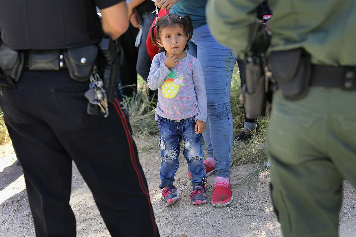 """A Mission Police Dept. officer (L), and a U.S. Border Patrol agent watch over a group of Central American asylum seekers before taking them into custody on June 12, 2018 near McAllen, Texas. U.S. border authorities are executing the Trump administration's """"zero tolerance"""" policy towards undocumented immigrants."""
