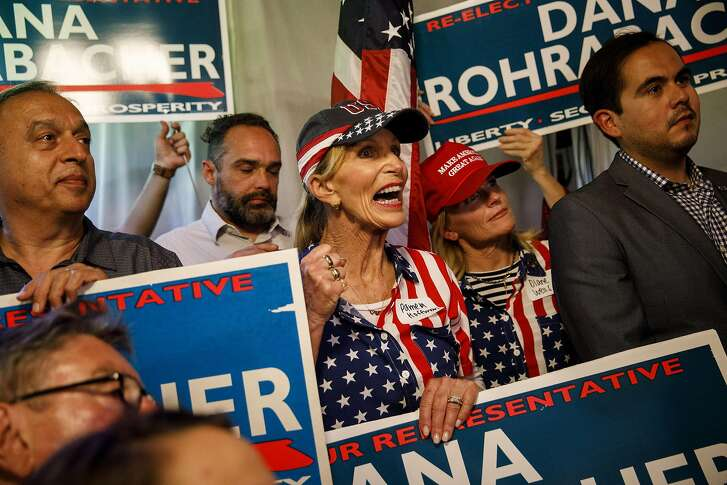Attendees hold signs and cheer during a primary election watch party for Dana Rohrabacher, Republican U.S. Senate candidate from California, not pictured, in Costa Mesa, California, U.S., on Tuesday, June 5, 2018. California's jungle primary is living up to its name in Orange County, where a former protege of 15-term Rohrabacher is among the names on a crowded June 5 ballot. Photographer: Patrick T. Fallon/Bloomberg