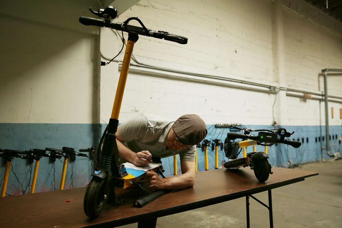 Technician Nate Booth runs maintenance on a scooter at Skip, Friday, June 15, 2018, in San Francisco, Calif. Skip, a scooter rental, is one of 12 companies applying for a permit to have an e-scooter program in the city.